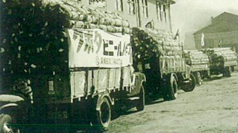 The first shipment on trucks lined up in front of the vinyl pipe plant's office